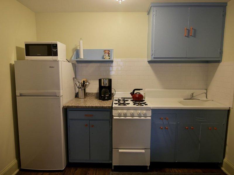 Cozinha urbana com fogão a gás, microondas e geladeira de eficiência.
