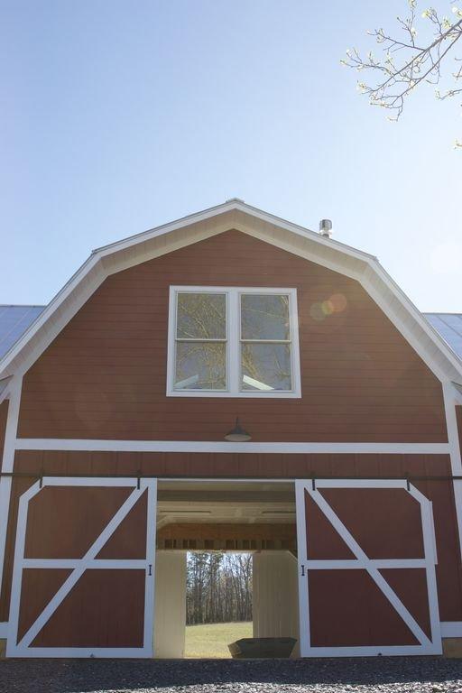 El granero con las puertas correderas abiertas. Los alojamientos están arriba.