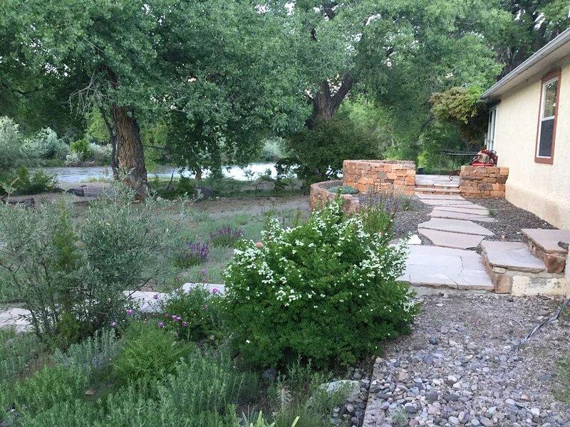 Back yard w/ gazebo, flowers & Rio Grande.