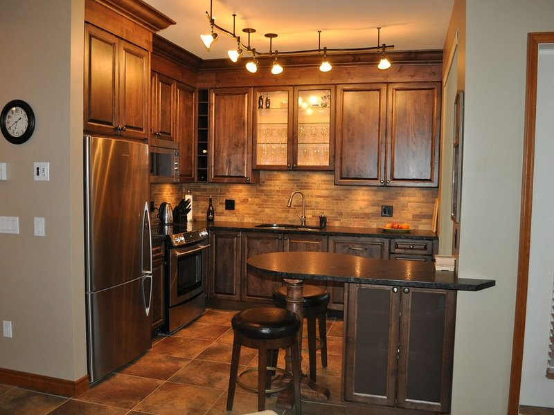 Vackert gourmetkök med bänkskivor i granit och rostfria vitvaror