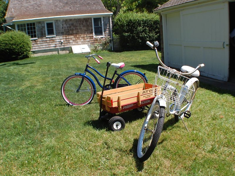 There are 4 bicycles, beach chairs, a beach umbrella and a radio flyer wagon