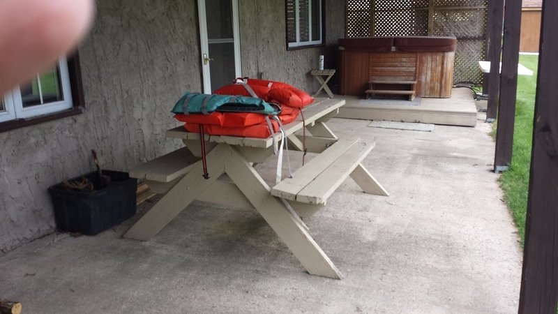 picnic table, life jackets, hot tub on covered patio