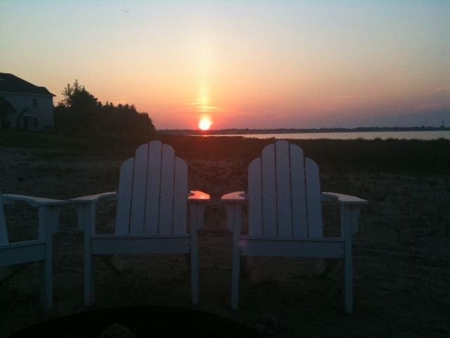 Sentado en la playa viendo la puesta de sol detrás del puente Mackinaw impresionante