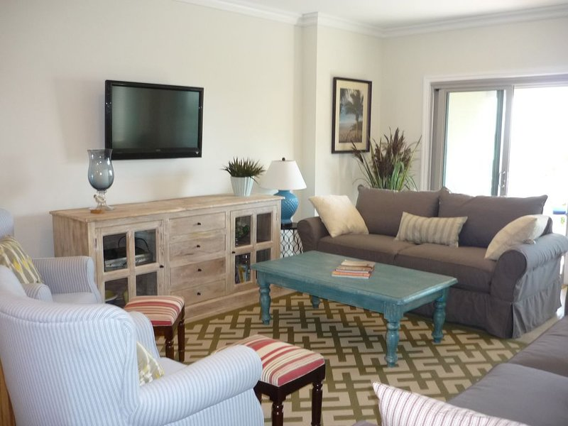 Bright, newly decorated living with beach view, comfortable seating.