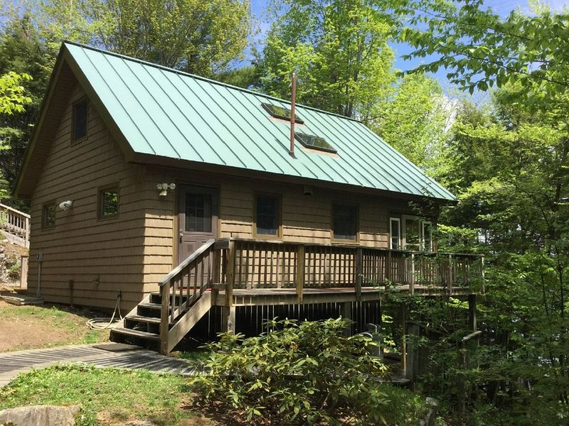 Side and rear view of cabin and deck to enclosed porch facing woods and lake