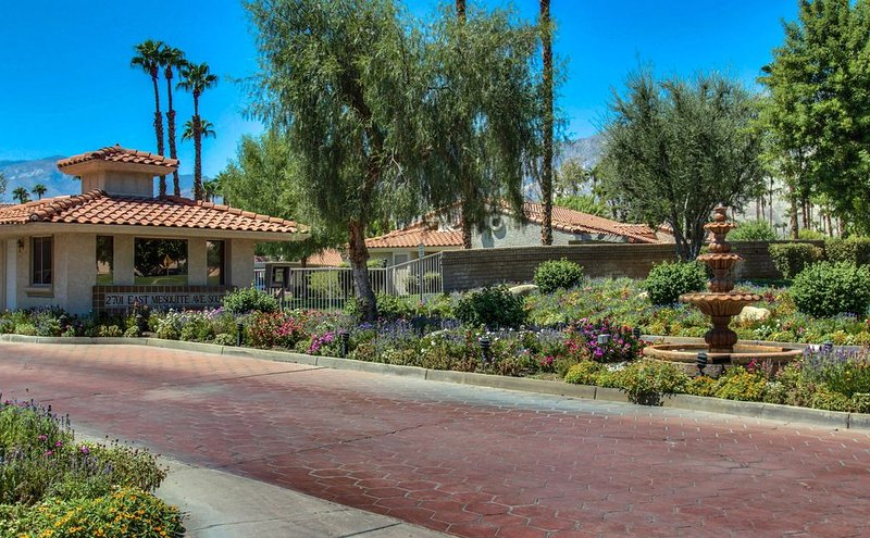 Private, gated community entrance with lush desert landscaping