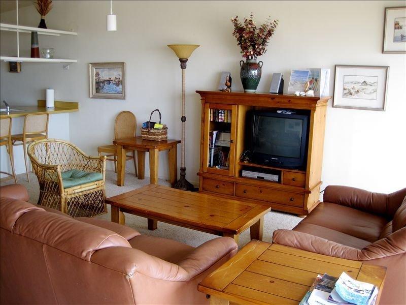 Amplia sala de estar con centro de entretenimiento y vista al mar.