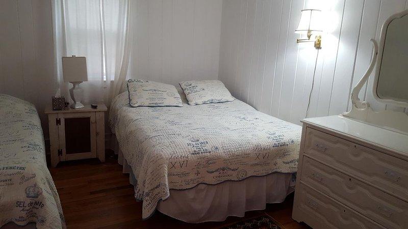 Dormitorio con cama queen y una TV simple e inteligente.