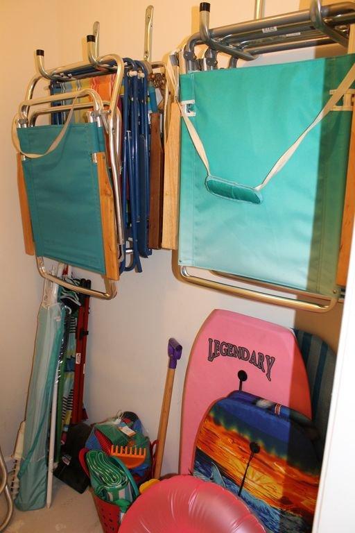 Armario de almacenamiento con sillas, sombrillas y juguetes para su uso.