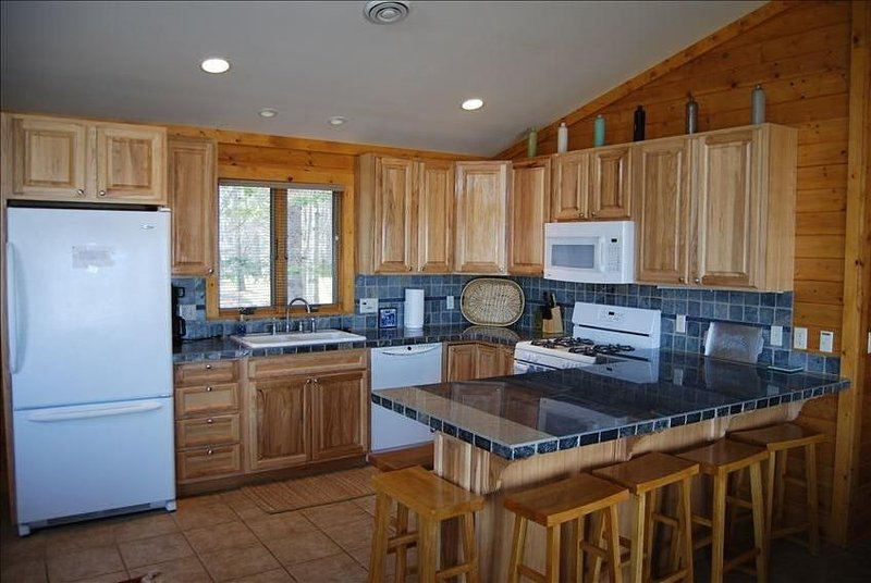 Kitchen bar area, open floor plan to living room, dining room. Fully stocked.