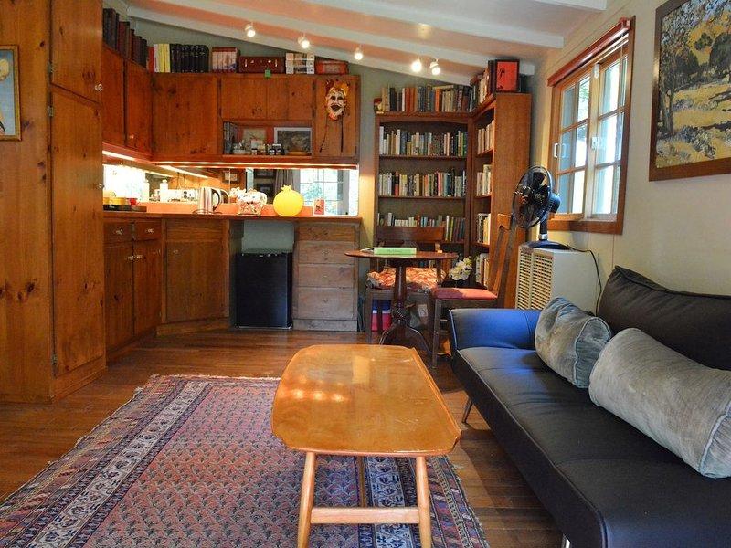 Canapé causeuse dans le salon / kitchenette. Stores et écrans.