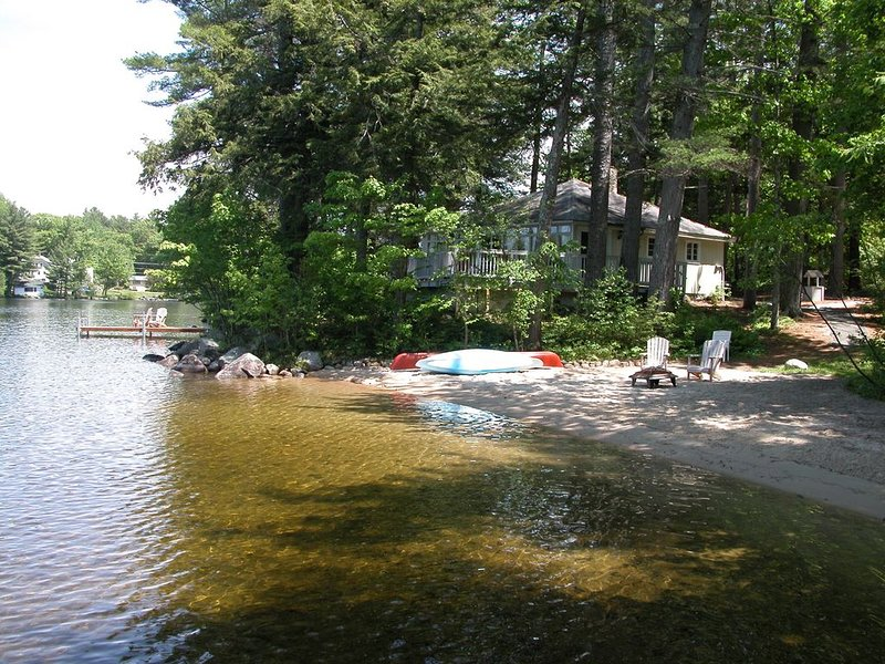 view of cottage showing the all sand beach, separate dock and lakefront deck