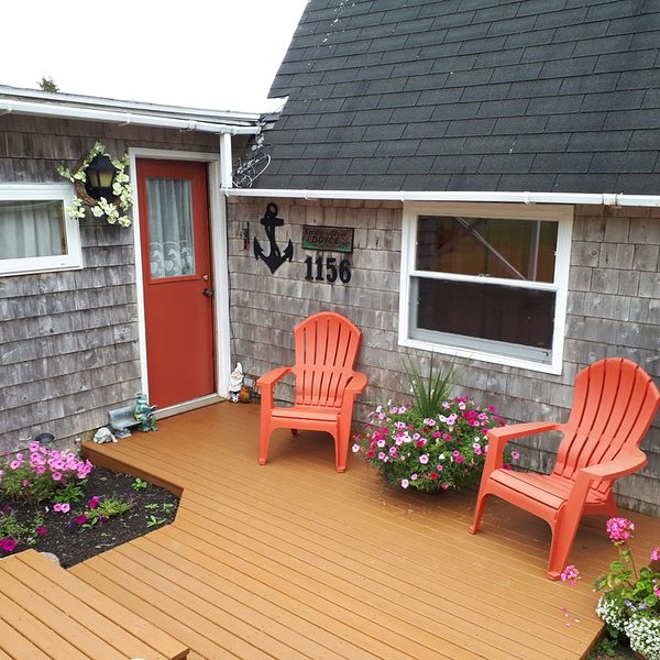 Front porch welcome with flowers and comfortable chairs.