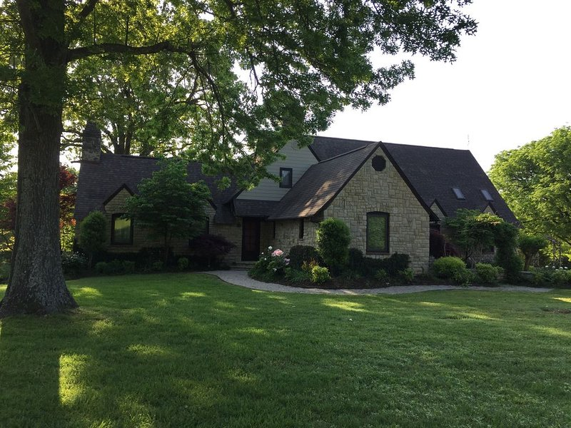 Front of home, facing expansive field and shaded yard.
