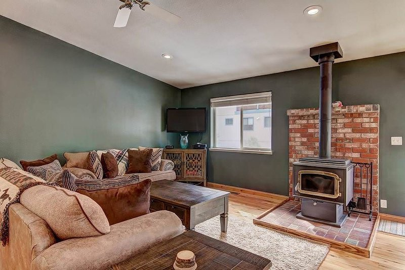 Living room with woodstove fireplace, flat screen TV, board games