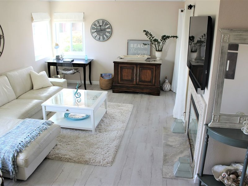 Enter to living room with ocean view window, fireplace, 60' TV,  access to patio