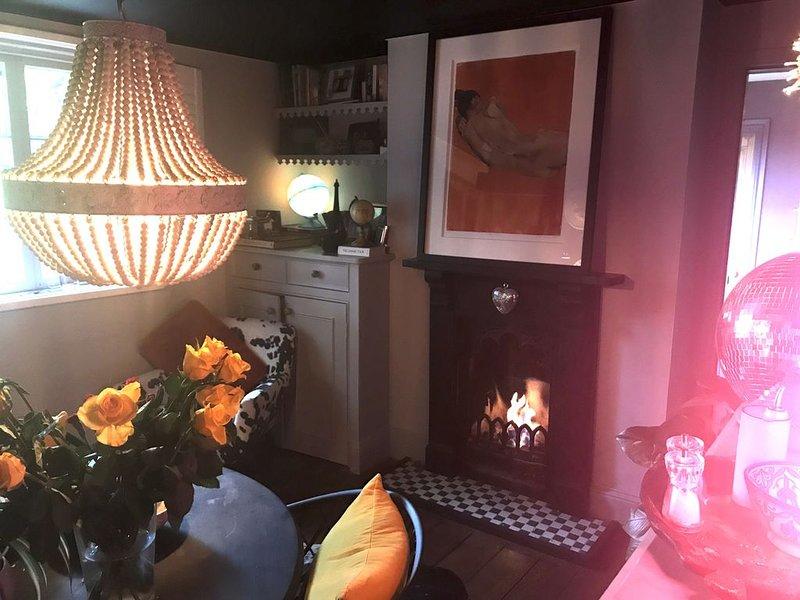 Salle à manger confortable avec banquette et feu au gaz. La chambre donne sur le jardin