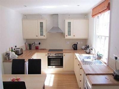 Volledig ingerichte lichte en zonnige open keuken naar terras aan de achterzijde met tafel / stoelen