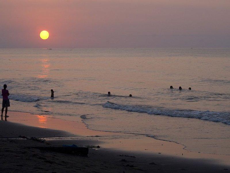 Zwemmen in de zee met zonsondergang voor de villa