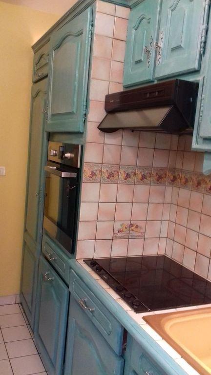 Cocina equipada con horno, nevera grande y vitrocerámica.