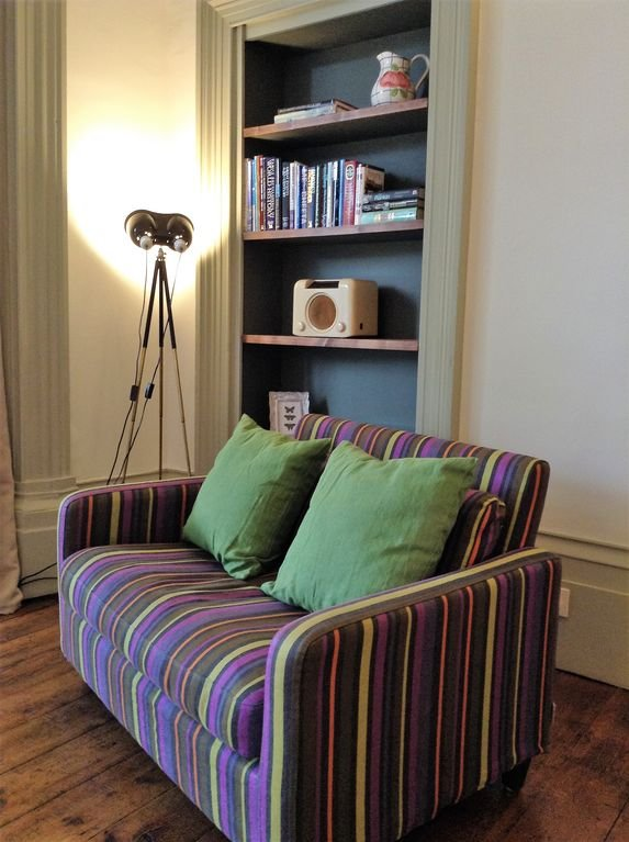 little sofa and lots of books in bedroom