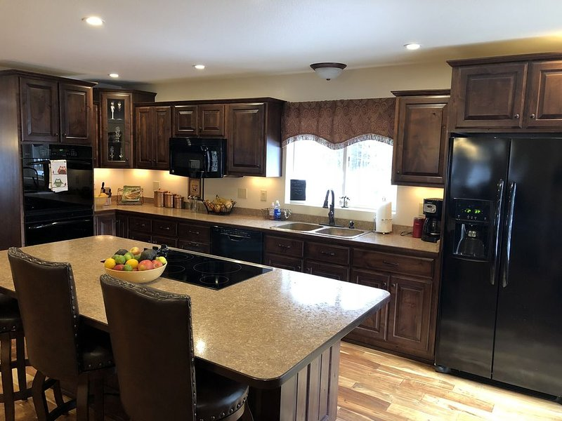 Kitchen with island cooktop and new appliances