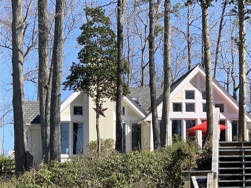 Front de rivière de la maison avec des murs de fenêtres à l'eau bleue