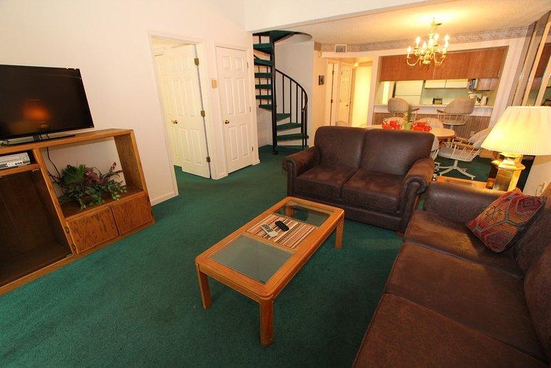 Salon et salle à manger et escalier menant à l'étage mezzanine