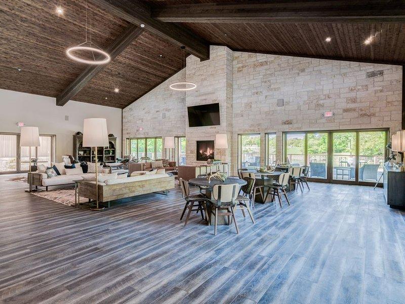 Grande salle joliment décorée avec télévision, cheminée, bar et accès au pont.