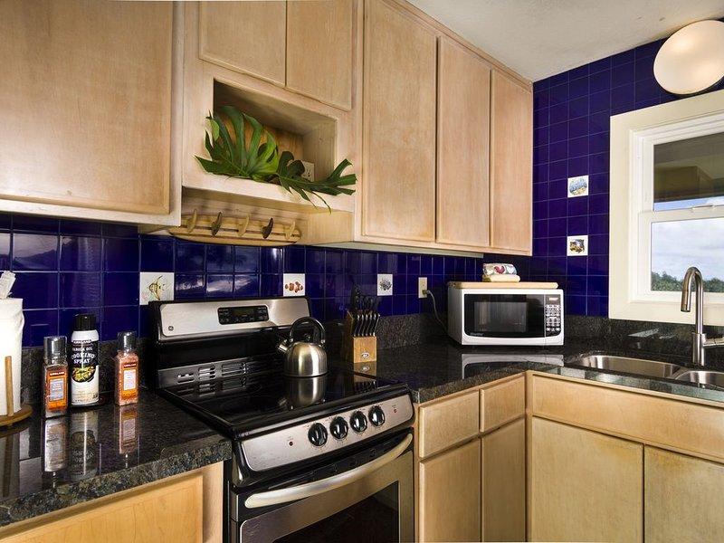 Cuisine complète avec cuisinière à 4 brûleurs et réfrigérateur standard.