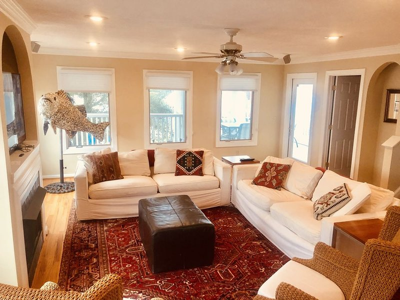 "Large living room with fireplace, smart 51"" HDTV, and door to second floor deck"