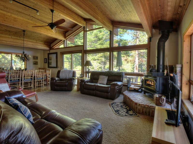 Living room with floor to ceiling windows and wood fireplace