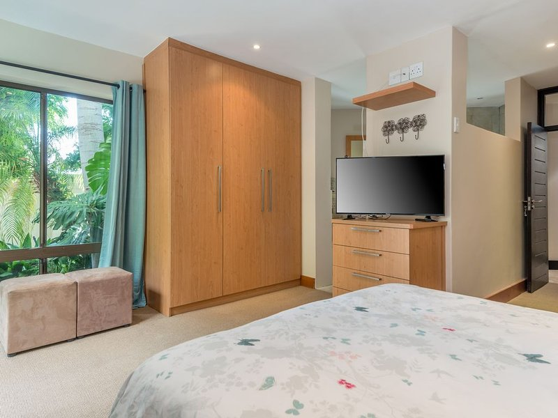 Bedroom 1 with full en-suite bathroom and sliding door leading to swimming pool