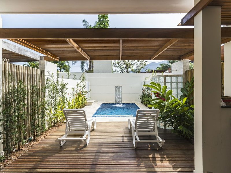 Recreation area with barbecue, pool, deck and wooden pergola.