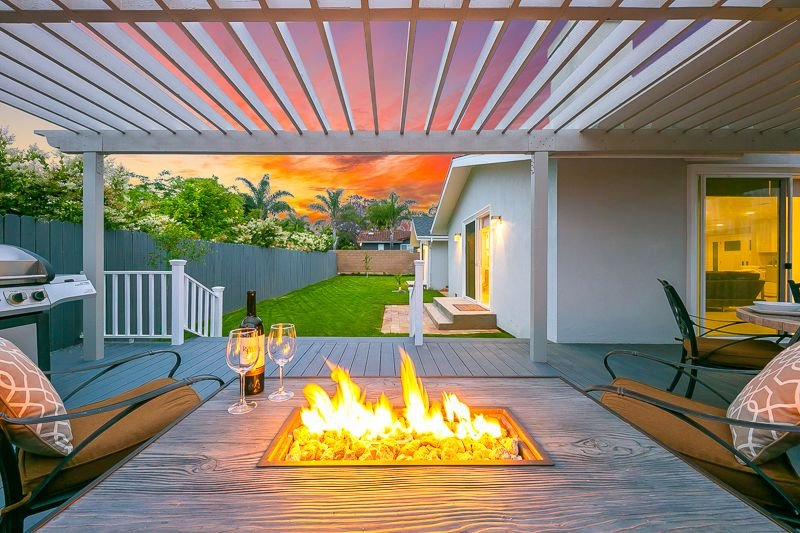 Patio features a beautiful fire pit and a barbecue, as well as a view of the serene yard.