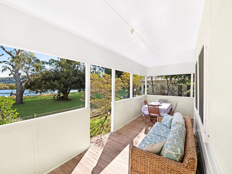 Outdoor seating and dining area overlooking Patonga Creek