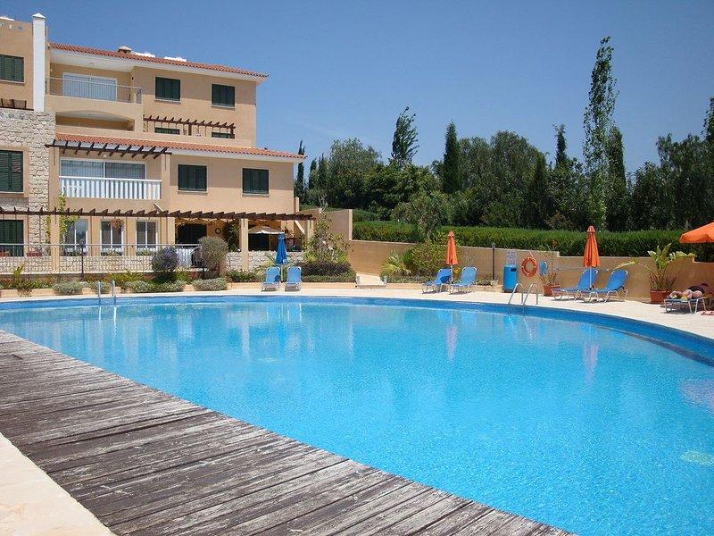 Grande piscina comum com espreguiçadeiras e guarda-sóis fornecidos desde