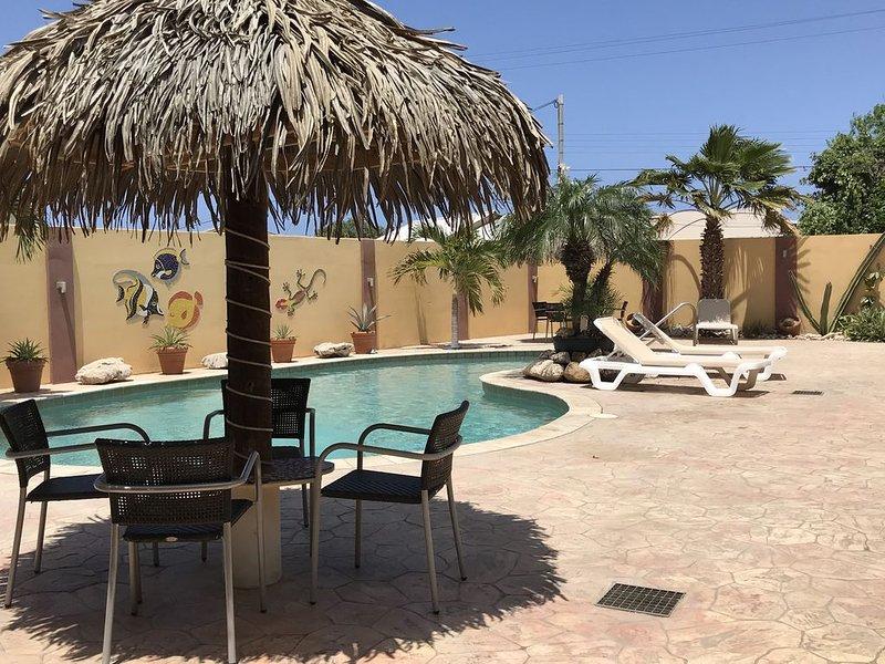 Jardín interior tropical con piscina, tumbonas y asientos.