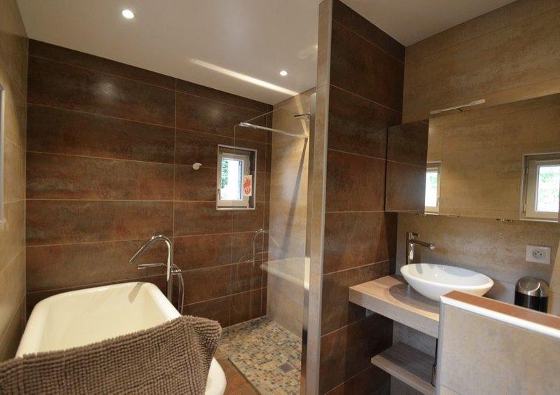Cuarto de baño: bañera y ducha a ras de suelo.