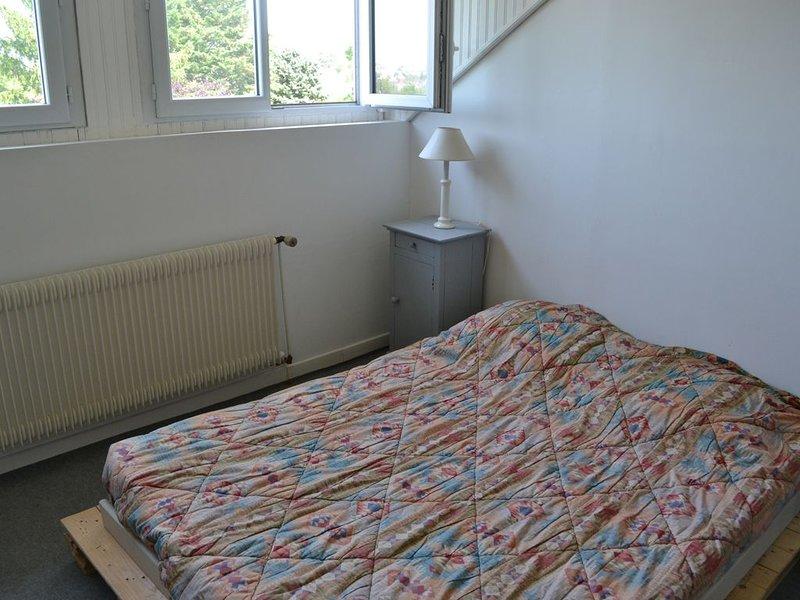 slaapkamer met tweepersoonsbed met uitzicht op de tuin