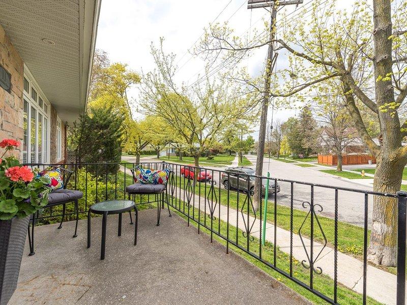 Porche en la puerta principal con una pequeña sala de estar para disfrutar de hermosas vistas del vecindario.