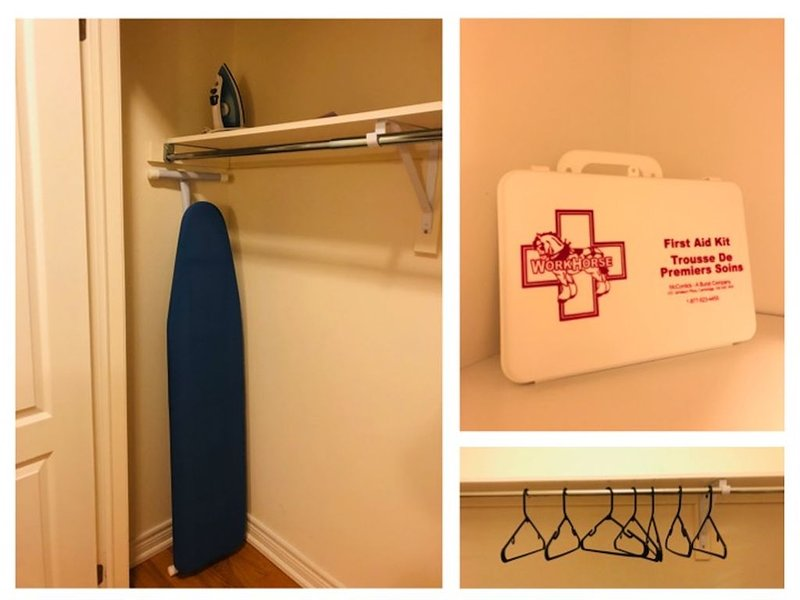 Closet with first aid box, iron, iron board and hangers.