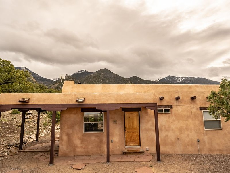 Front of the house with the Sangre de Cristos behind it.