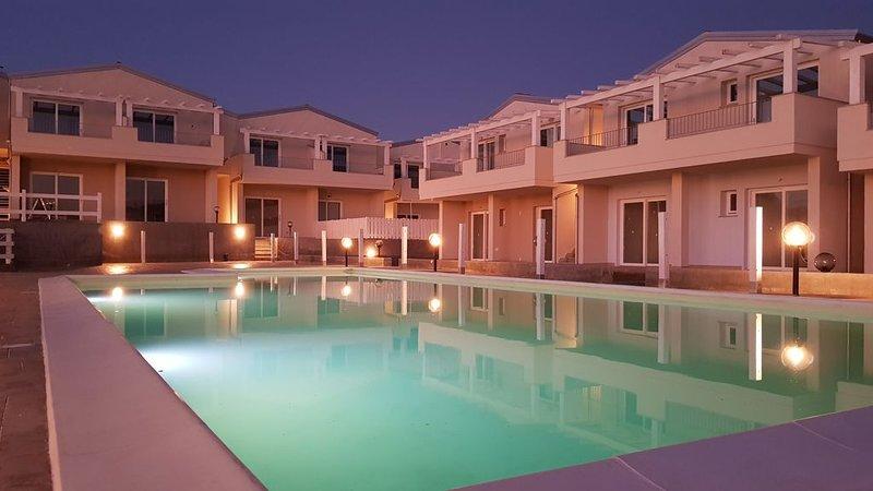 Delizioso trilocale piano terra in residence con piscina, con giardino arredato, location de vacances à Santa Maria Coghinas