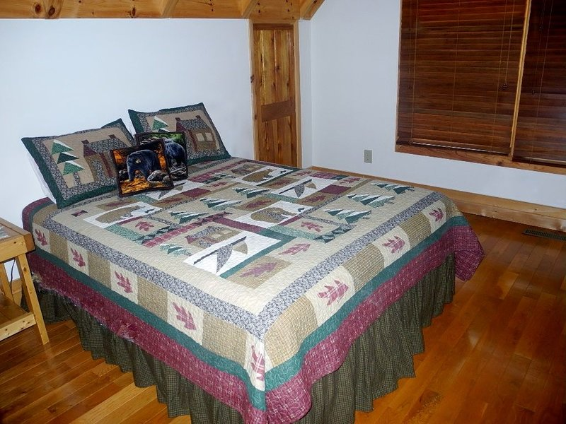 Upper level bedroom with queen bed. View coming into room.