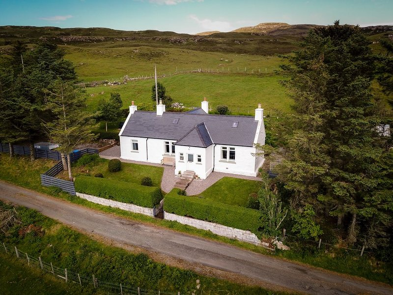 Traditional croft house sitting in elevated position overlooking Loch Snizort