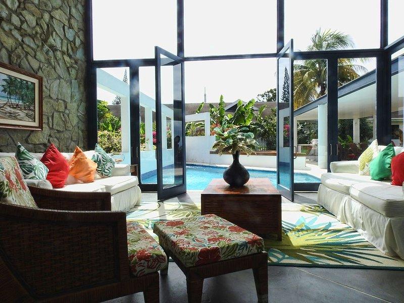 Vardagsrum som leder till pool och veranda