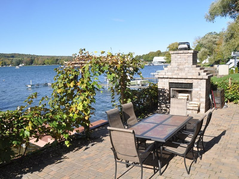 Patio by the lake with trellis to dock, dinning table and fireplace