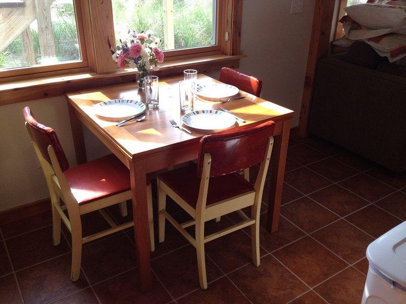 Table à manger avec des feuilles extensibles cachées en dessous.