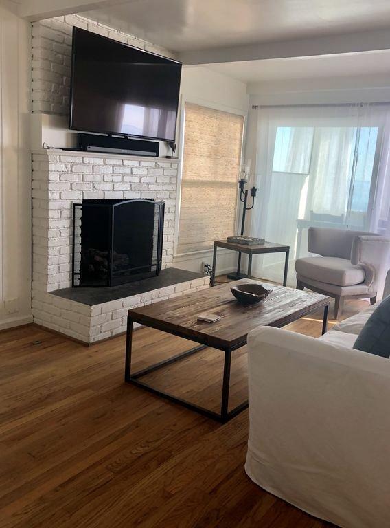 Salon Smart TV à écran plat avec Apple TV. Foyer au gaz de travail.